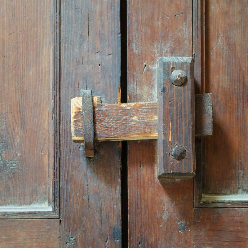 Close-up van een houten oude klink over een overladen houten deur royalty-vrije stock foto