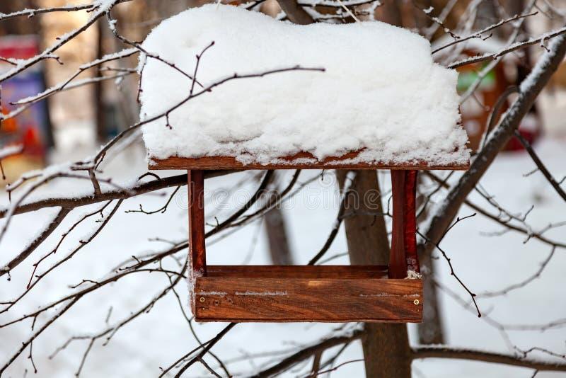 Close-up van een houten voeder van de vogelhuisvogel die met een grote laag van sneeuw op een duidelijke de winterdag wordt behan stock foto