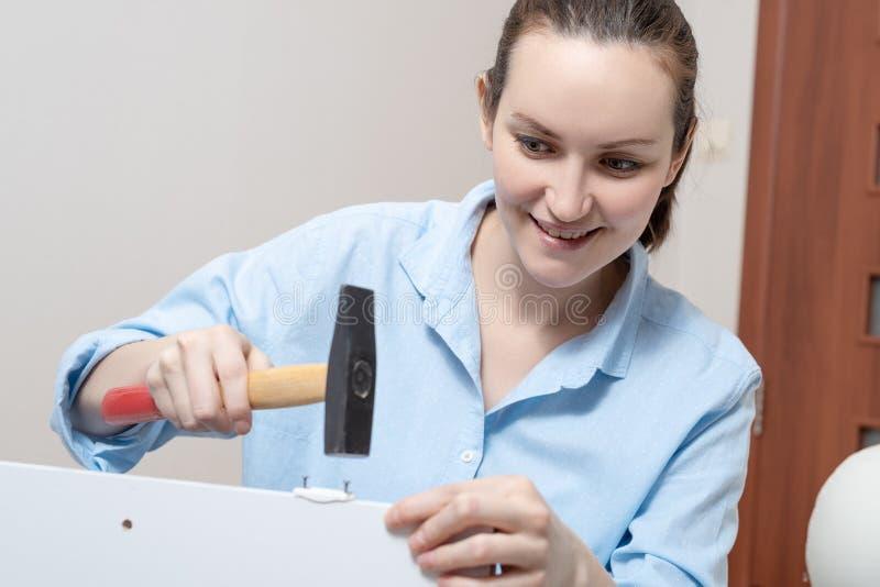 Close-up van een jonge vrouw met een hamer, meubilairassemblage stock foto