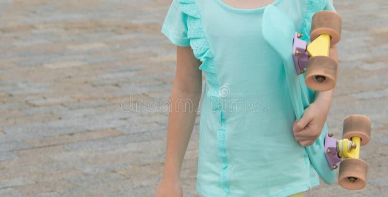 Close-up van een kind, meisjes en skateboardtorso, tegen een achtergrond van steenbetonmolens royalty-vrije stock afbeeldingen