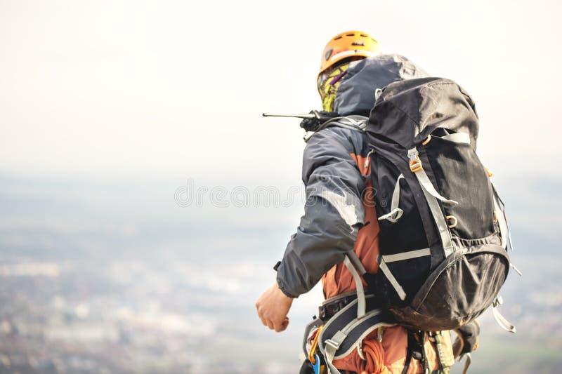 Close-up van een klimmer van de rug in toestel en met een rugzak met materiaal op de riem, tribunes op een rots, bij hoogte stock afbeelding