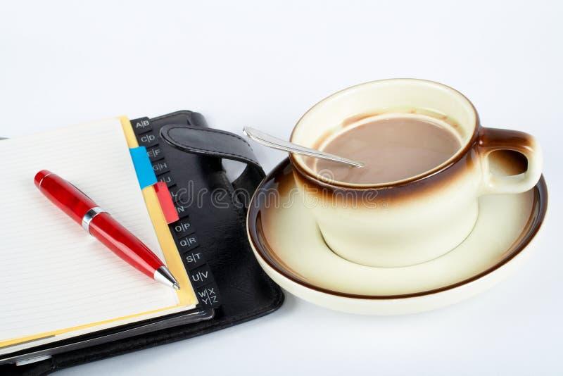 Close-up van een kop van koffie met de lepel binnen en notitieboekje met ballpoint stock foto