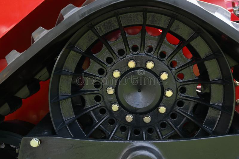 Close-up van een landbouwmachinesband met op een oranje wiel stock afbeelding