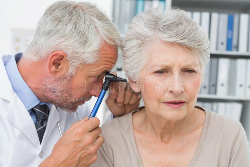 Close-up van een mannelijke arts die het oor van de hogere patiënt onderzoeken royalty-vrije stock afbeeldingen