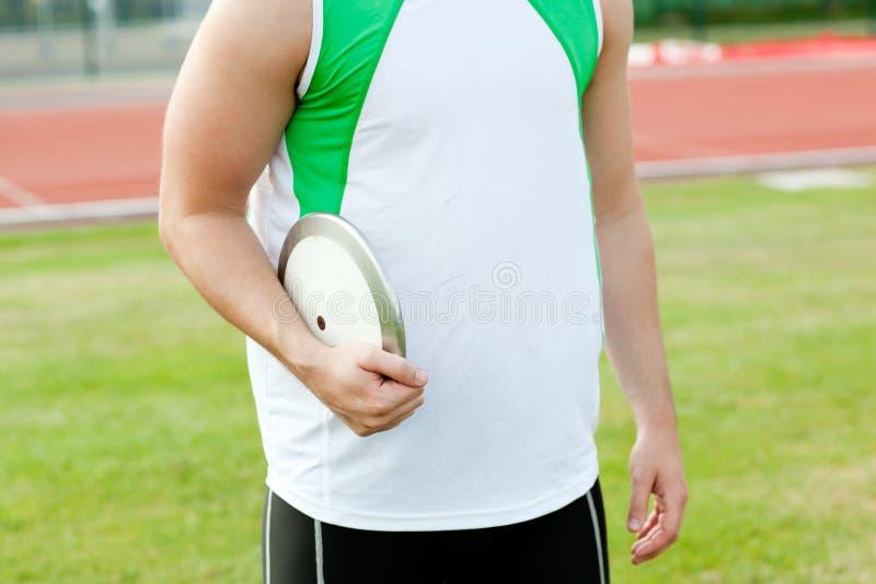 Close-up van een mannelijke atleet die een discus houdt stock foto's