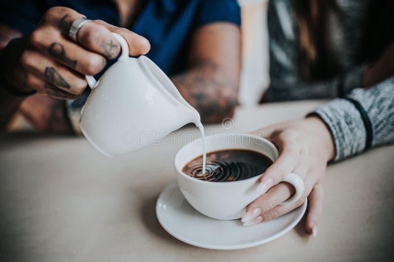 Close-up van een mannelijke gietende melk in de koffie die van het wijfje wordt geschoten stock foto