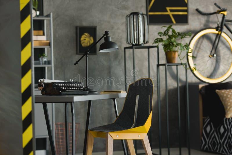 Close-up van een moderne, gele stoel bij een grijs bureau met een typewri stock foto