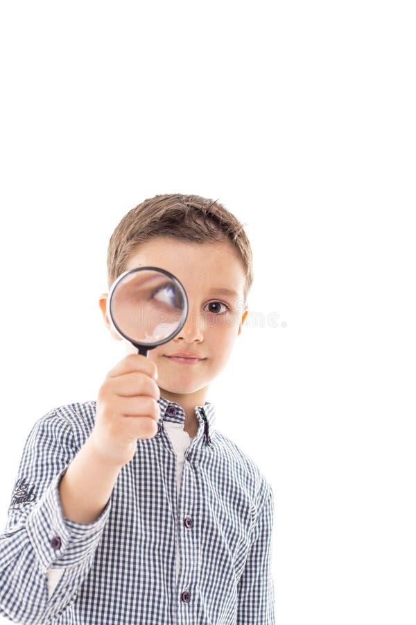 Close-up van een mooi kind die door een vergrootglas kijken royalty-vrije stock afbeelding