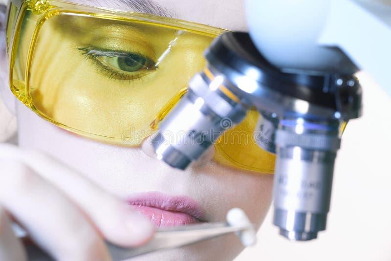 Close-up van een mooi laboratoriummeisje in gele beschermende glas royalty-vrije stock foto