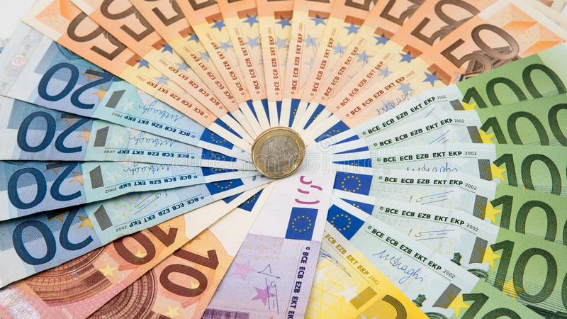 Close-up van een muntstuk één euro met bankbiljetten van verschillende waarden Het Geld van het contante geld stock foto's