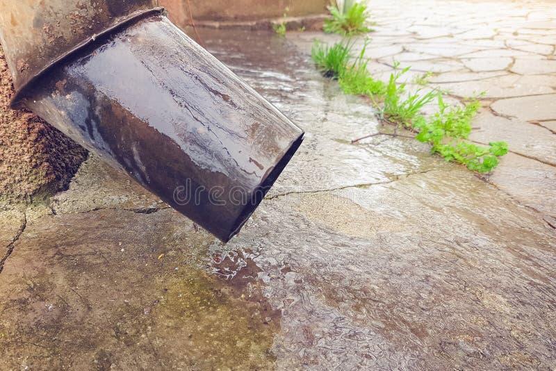 Close-up van een rioolbuis en een natte vloer van een landelijke binnenplaats royalty-vrije stock afbeelding
