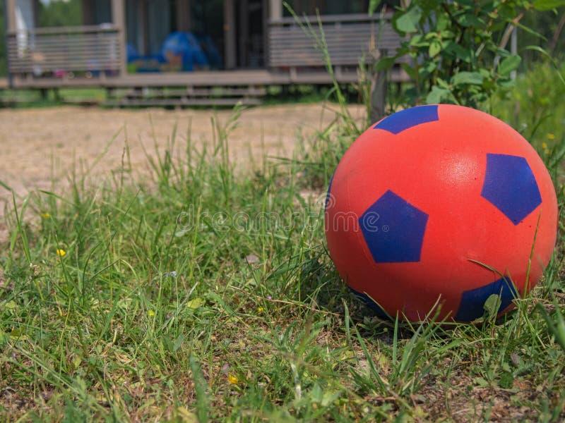 Close-up van een rode voetbalbal voor kinderen op het groene gras voor een buitenhuis Portiek van het huis op de achtergrond royalty-vrije stock foto