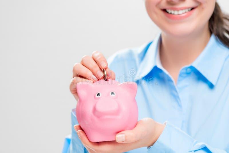 Close-up van een roze varkensspaarvarken in de handen van economisch royalty-vrije stock afbeelding