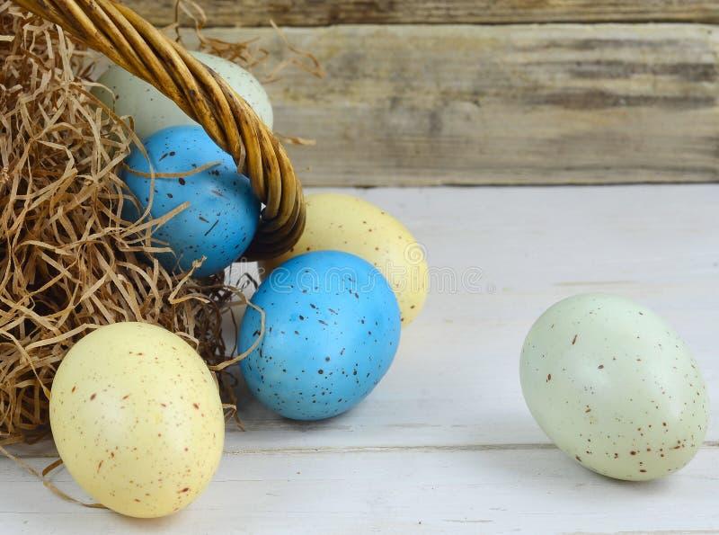 Close-up van een rustieke Pasen-mand met pakpapiergras en blauwe, groene en gele bevlekte of gespikkelde eieren op vergoelijkt stock afbeelding