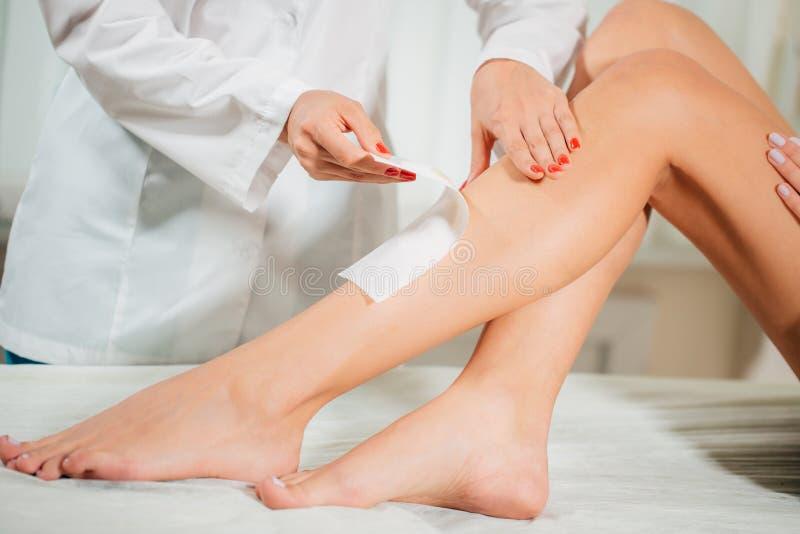 Close-up van een Schoonheidsspecialist Waxing Woman Leg met Wasstrook in Beauty Spa stock foto's