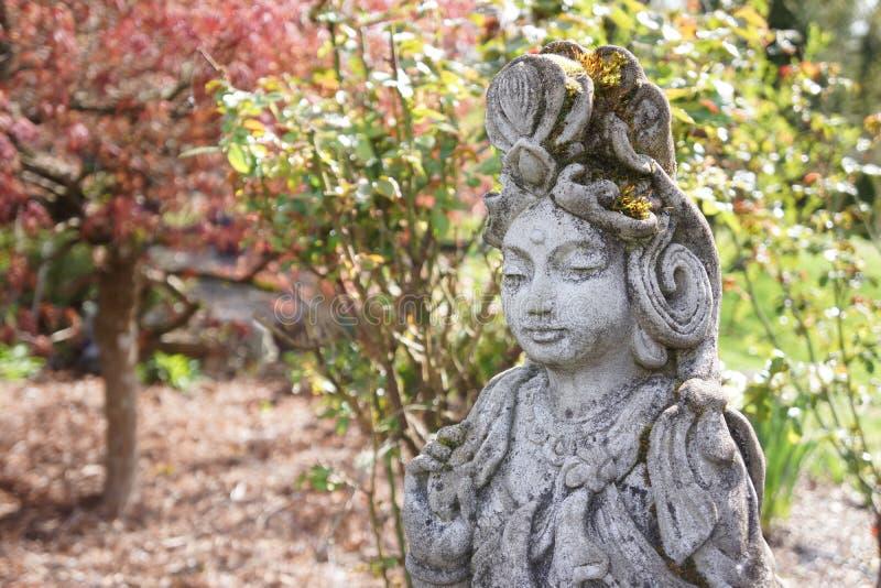 Close-up van een standbeeld van Kwan Yin met rode esdoorn royalty-vrije stock afbeeldingen