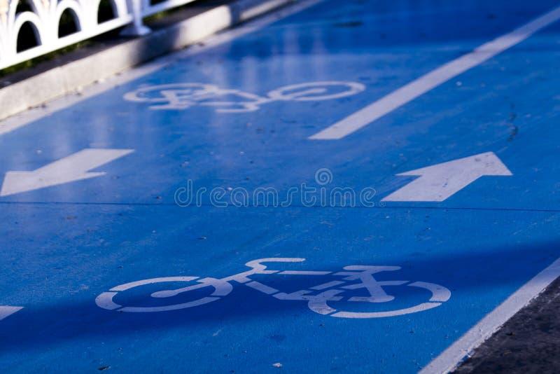 Close-up van een teken van de fietsroute in twee richtingen met het blauwe materiaal, de pijlen en de pictogrammen van de grondde stock afbeelding