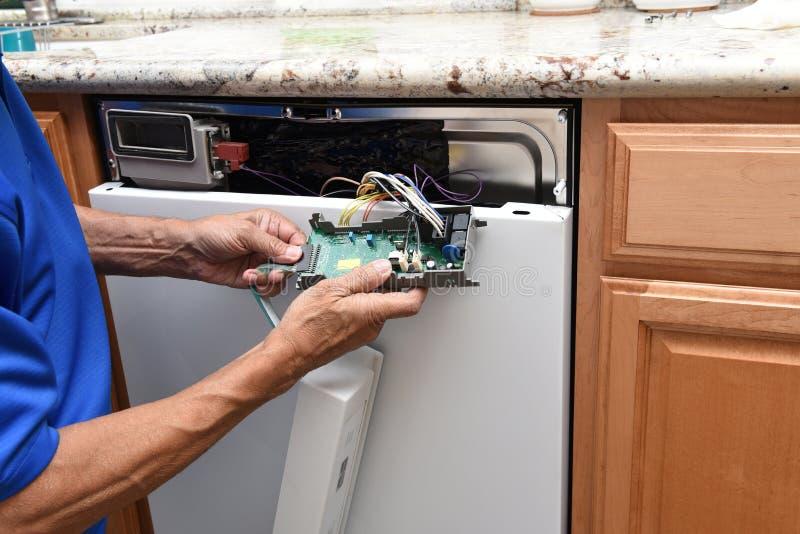 Close-up van een toestellenhersteller die het controlebord afsluiten aan een gebroken afwasmachine stock foto