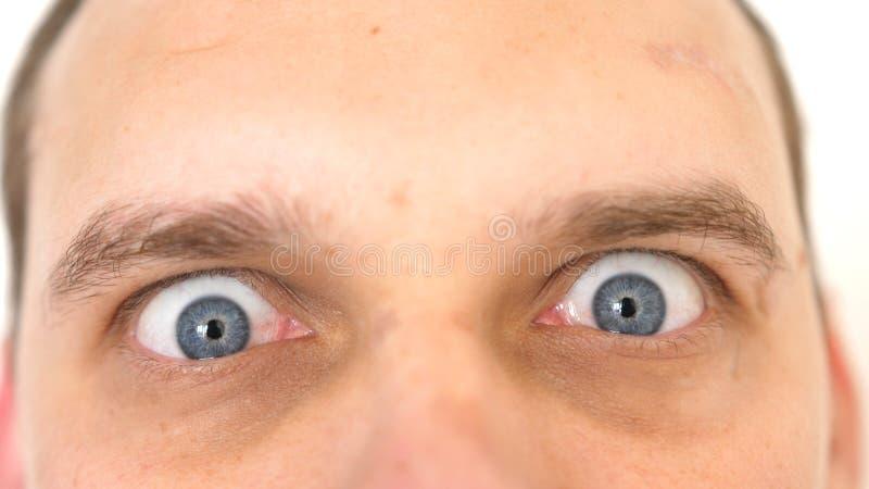 Close-up van een verraste emotionele mens die met blauwe ogen de camera onderzoeken royalty-vrije stock afbeelding