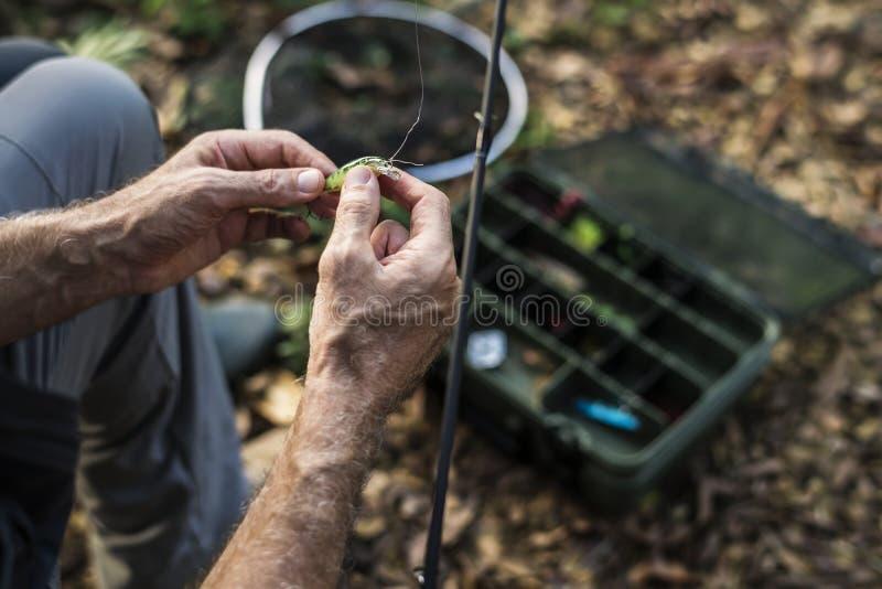 Close-up van een visser die op aas zetten stock afbeeldingen