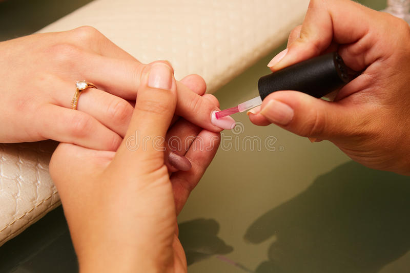 Close-up van een vrouw in een spijkersalon die een manicure ontvangen door een schoonheidsspecialist met nagelvijl wordt geschote stock foto