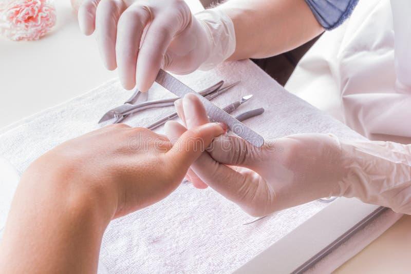 Close-up van een vrouw in een spijkersalon die een manicure ontvangen door een schoonheidsspecialist met nagelvijl wordt geschote royalty-vrije stock afbeeldingen