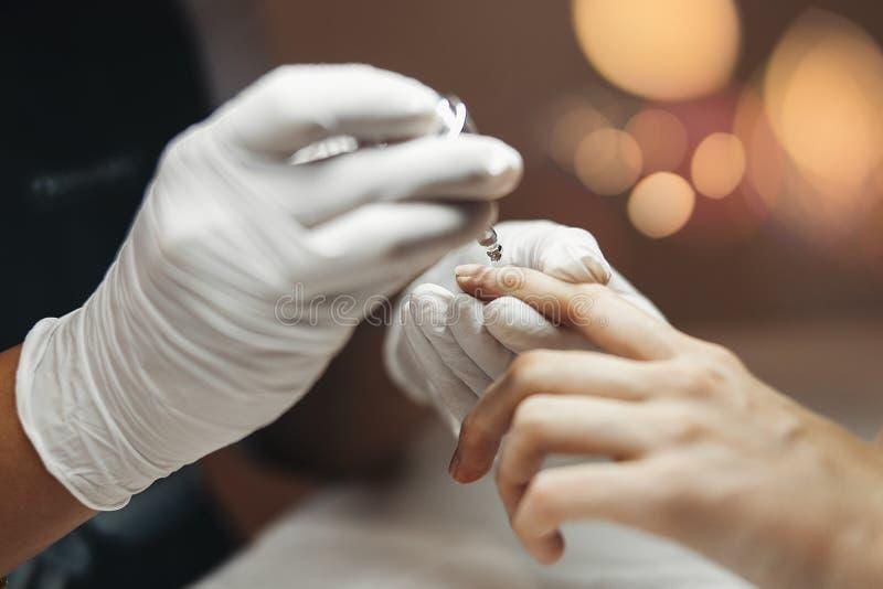 Close-up van een vrouw in een spijkersalon die een manicure ontvangen door een schoonheidsspecialist wordt geschoten die stock foto