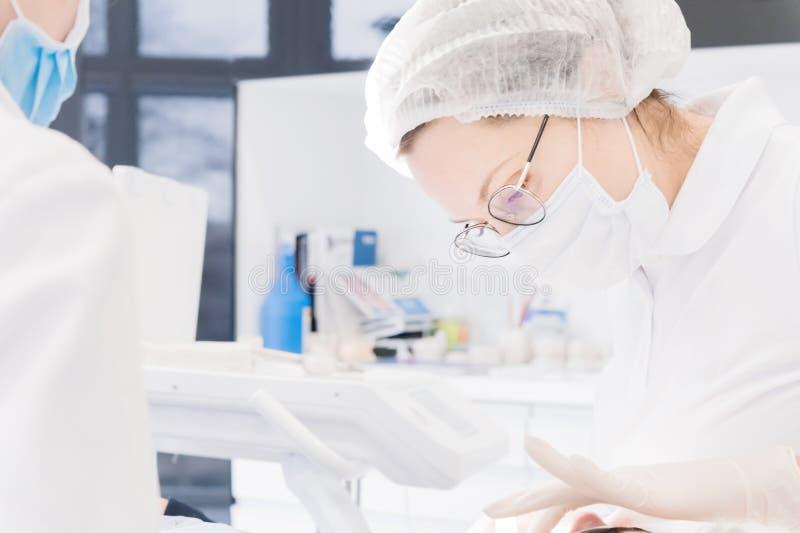 Close-up van een vrouwentandarts in het medische bureau die de mondholte van de patiënt onderzoeken stock afbeelding