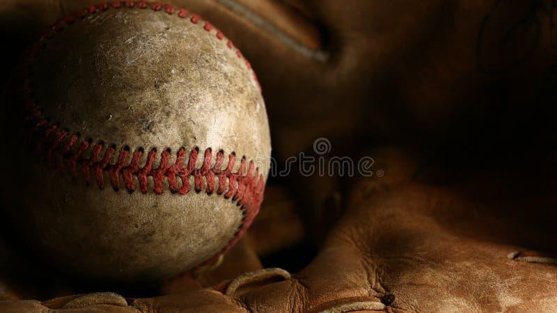 Close-up van een vuil, oud honkbal met rode naden op een bruine leerhandschoen royalty-vrije stock fotografie