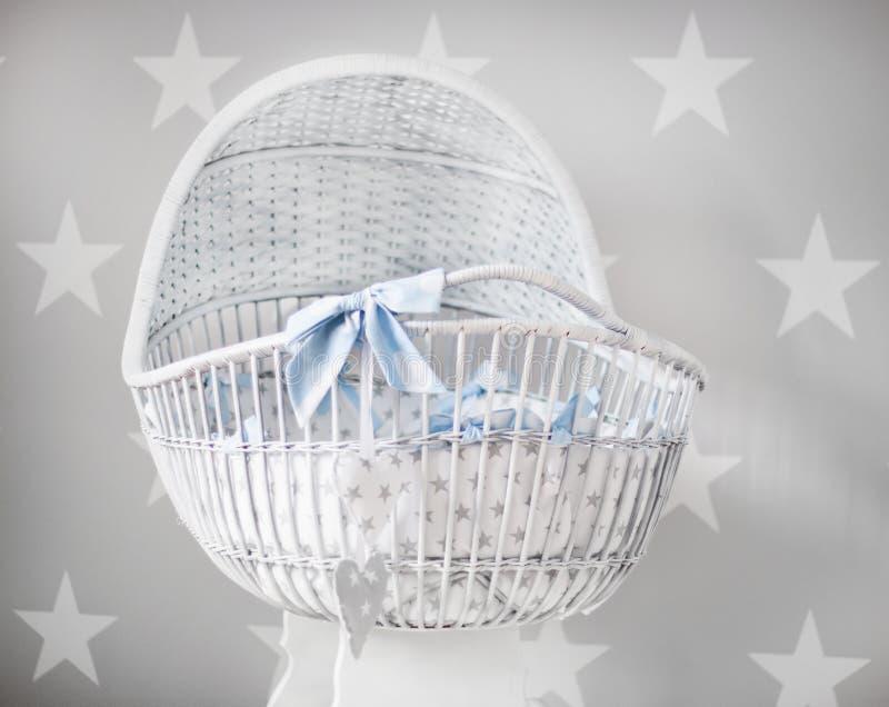 Close-up van een witte kleine babywieg met blauwe linten en sterren op de achtergrond royalty-vrije stock afbeelding