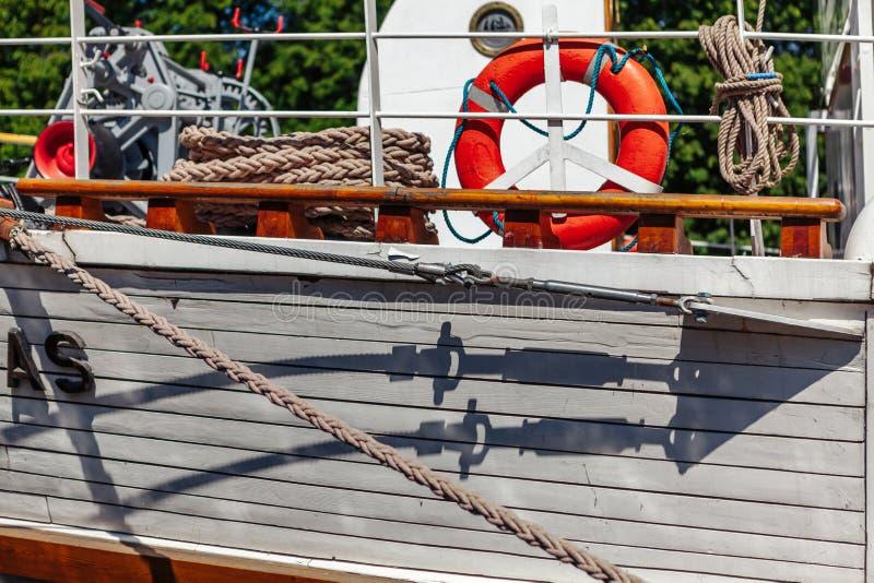 Close-up van een zeilboot` s kant met gloed van water Klaipeda, Litouwen stock fotografie