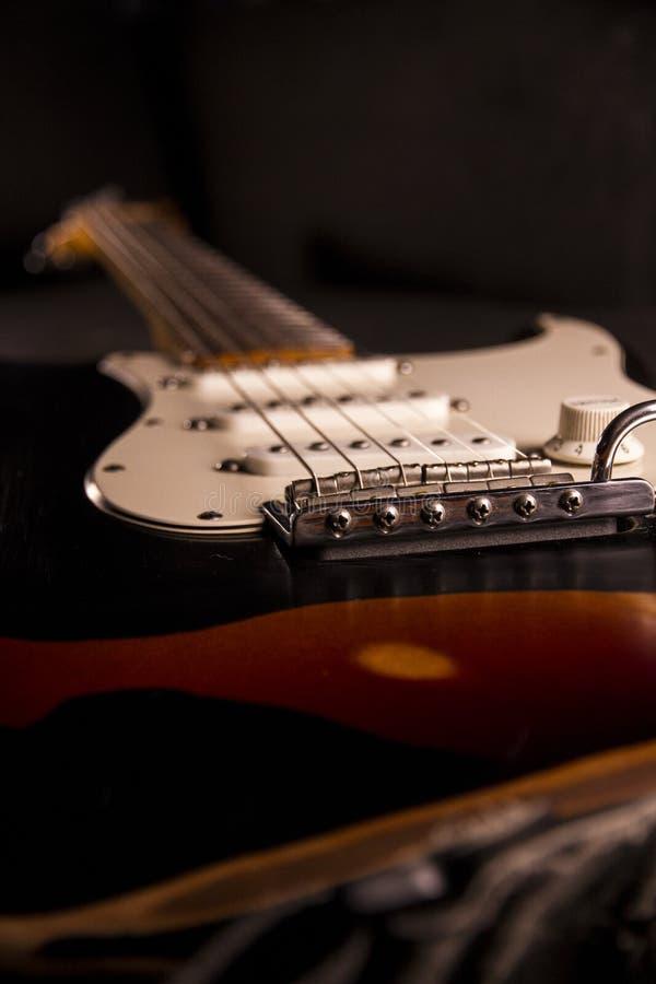 Close-up van een zonnestraal-gekleurde elektrische die gitaar met zwarte die verf wordt behandeld op bepaalde punten wordt verwij stock fotografie