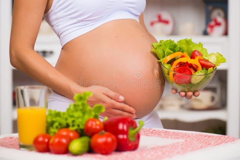 Close-up van een zwangere buik De Gezondheid van vrouwen, versterkt voedsel royalty-vrije stock foto