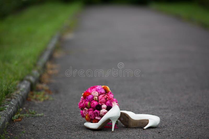 Close-up van elegante witte huwelijksschoenen en een vers boeket wordt geschoten dat royalty-vrije stock afbeelding