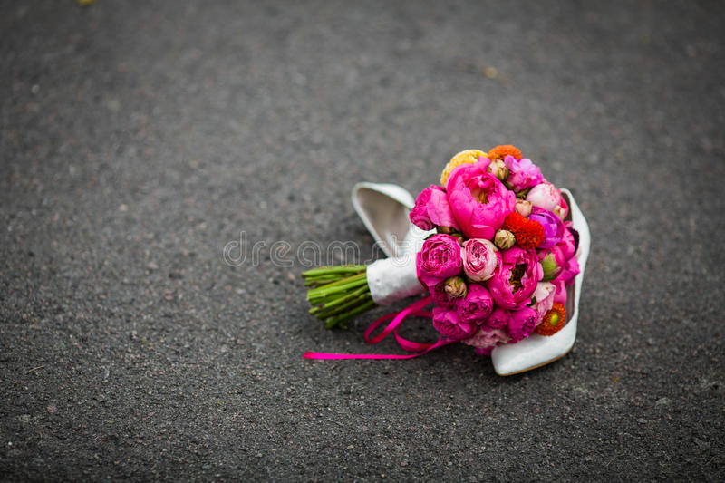 Close-up van elegante witte huwelijksschoenen en een vers boeket wordt geschoten dat stock fotografie