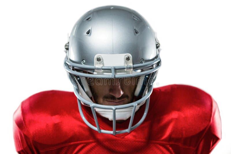 Close-up van ernstige Amerikaanse voetbalster die in rood Jersey neer kijken royalty-vrije stock fotografie