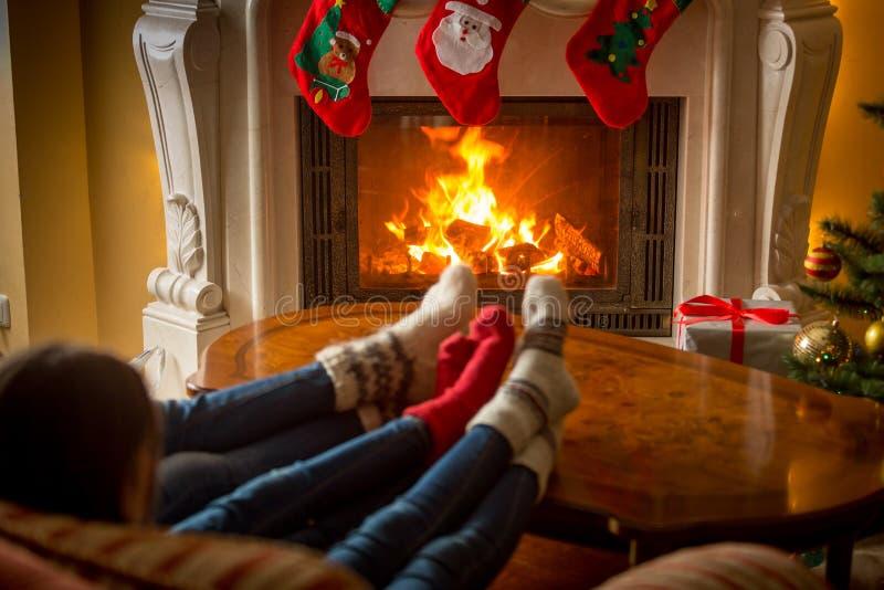 Close-up van familie in comfortabele gebreide sokken die bij open haarddec verwarmen royalty-vrije stock fotografie