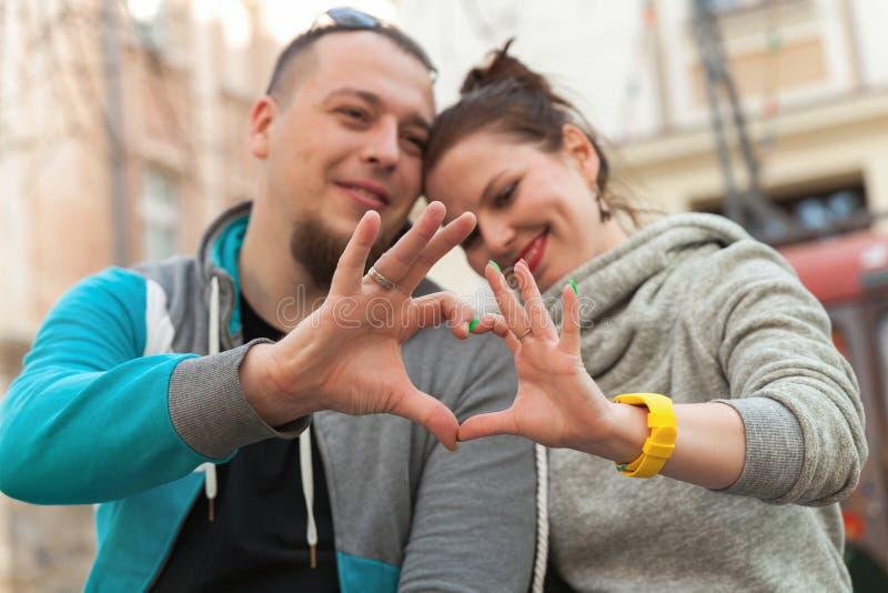Close-up van familiepaar die hartvorm met handen maken Gelukkig romantisch jong paar in liefde die een hart met vingers gesturing royalty-vrije stock fotografie