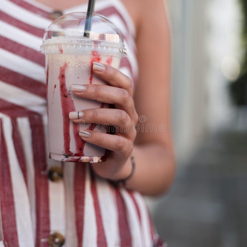 Close-up van frambozen zoete milkshake in de handen van een modieuze jonge vrouw Modieus meisje in een gestreepte kleding stock afbeelding