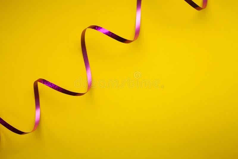 Close-up van gebogen purper glanzend lint op gele backgound stock foto's