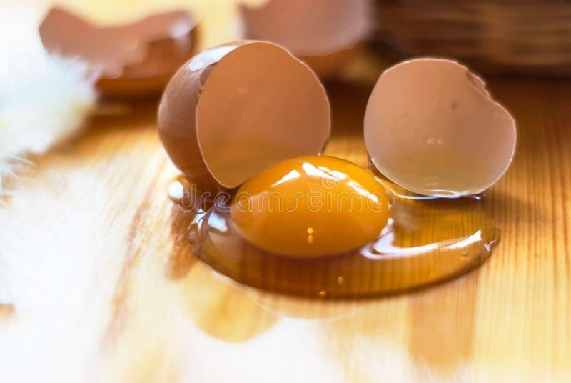 Close-up van gebroken ei op de keukenlijst, mand defocuses Gr. stock foto