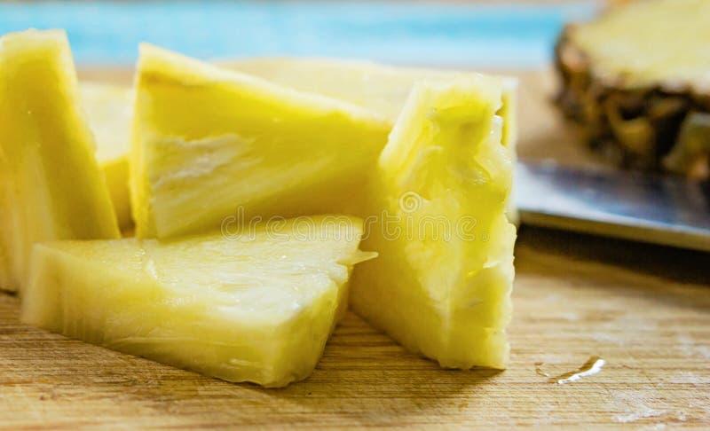 Close-up van gehakte ananas, driehoekige stukken op de keuken t stock afbeelding