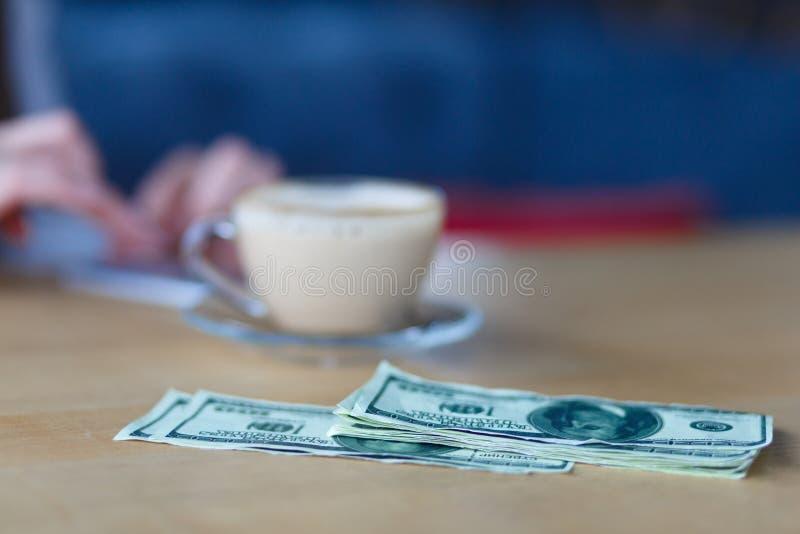 Close-up van geld op de lijst Geld en kop van koffie op de lijst stock fotografie