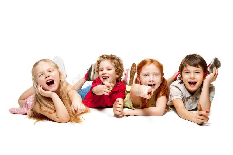 Close-up van gelukkige op vloer in studio liggen die en kinderen die omhoog kijken, op witte achtergrond wordt geïsoleerd royalty-vrije stock afbeeldingen
