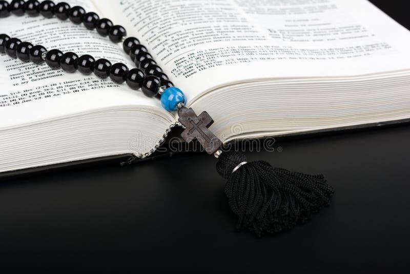 Close-up van geopende Heilige Bijbel en rozentuinparels met kruis op zwarte achtergrond Het concept van de godsdienst Boek en kru stock foto's
