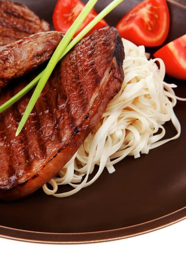 Close-up van geroosterd lapje vlees met deegwaren royalty-vrije stock fotografie