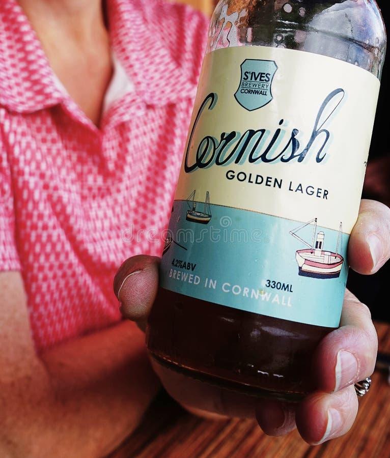 Close-up van Gouden die Lager Beer Bottle Van Cornwall door wijfje wordt gehouden royalty-vrije stock fotografie