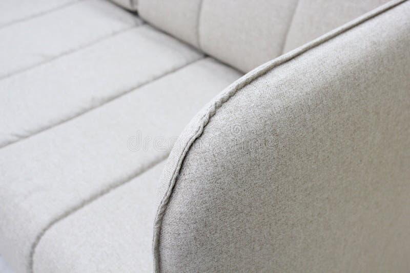 Close-up van grijze bank met armsteuntextiel, nieuw meubilair modern ontwerp met vrije ruimte voor tekst stock foto