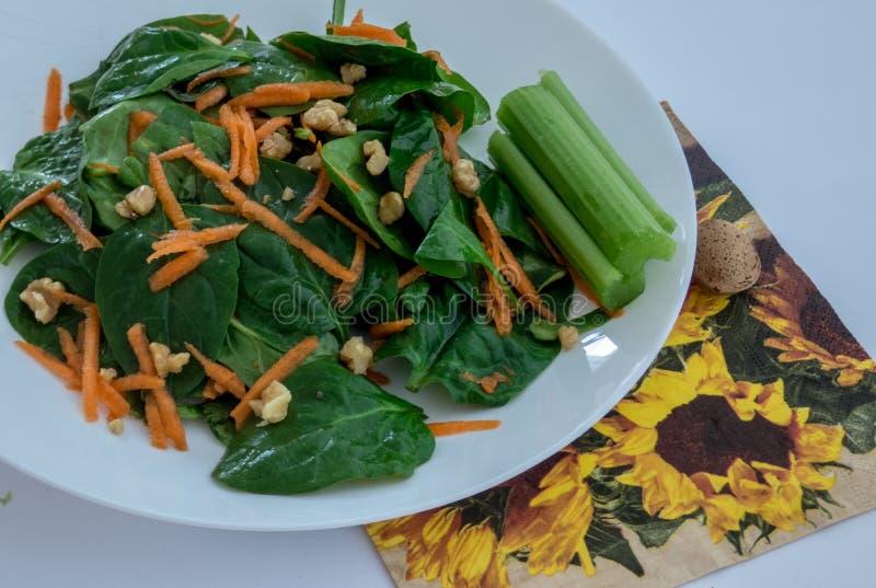 Close-up van groene salade met spinazie, wortel en noten met selderie royalty-vrije stock fotografie