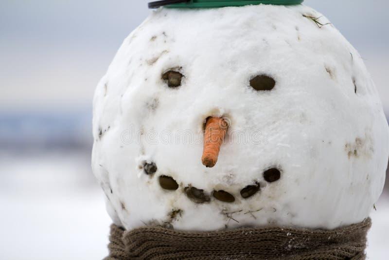 Close-up van groot grappig primitief het glimlachen sneeuwmanhoofd met wortel stock afbeeldingen